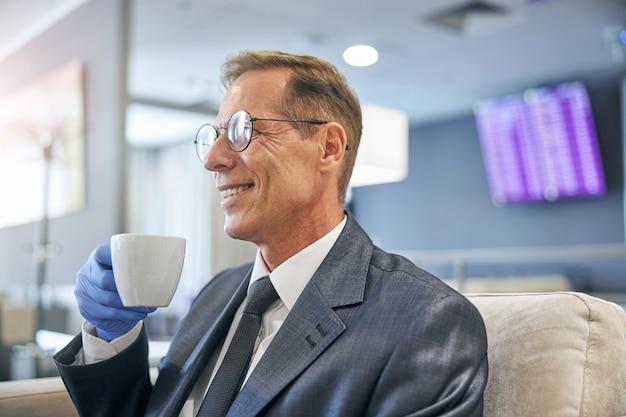 L'uomo felice con gli occhiali e l'abito elegante sta bevendo una tazza di bevanda calda mentre aspetta il volo con guanti di lattice