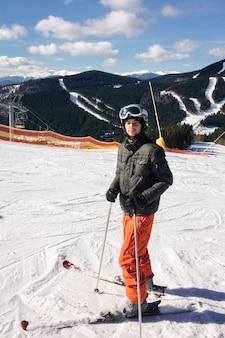Uomo felice in bicchieri in piedi con gli sci sulla neve nelle montagne dei carpazi. sullo sfondo di boschi e piste da sci con impianti di risalita. avvicinamento.