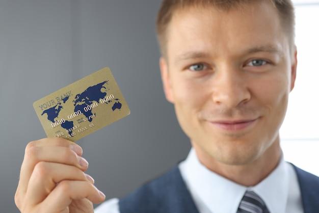 Uomo felice tenere in mano la carta di credito in plastica