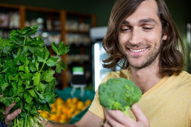 Broccoli felici della tenuta dell'uomo e mazzo di erbe e nella sezione organica
