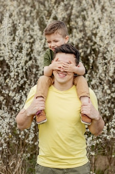 Uomo felice che tiene suo figlio divertendosi.