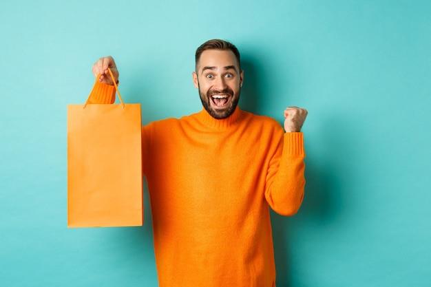 Uomo felice che tiene la borsa della spesa arancione e gioia, ha ottenuto lo sconto e festeggia, in piedi su sfondo turchese.
