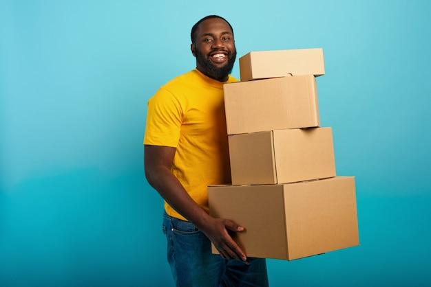 L'uomo felice tiene molti pacchetti ricevuti. sfondo ciano