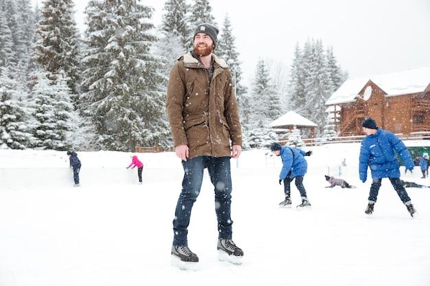 Uomo felice in pattini da ghiaccio che guarda lontano all'aperto con la neve with