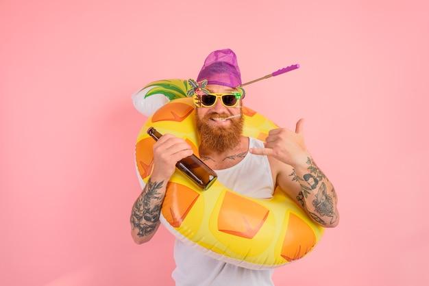 L'uomo felice è pronto a nuotare con una ciambella salvagente con birra e sigaretta