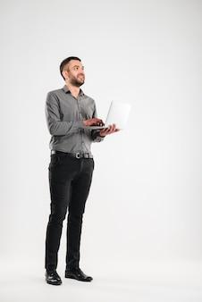 Uomo felice isolato per mezzo del computer portatile.