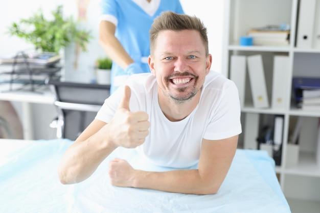 L'uomo felice si trova sul divano e mostra la sua classe di mano.