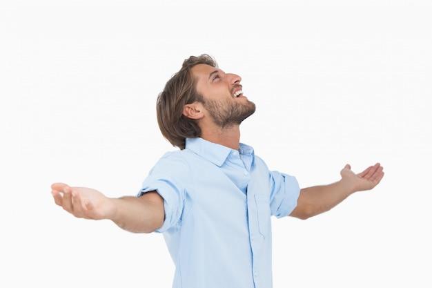 Uomo felice che osserva in su con le braccia distese