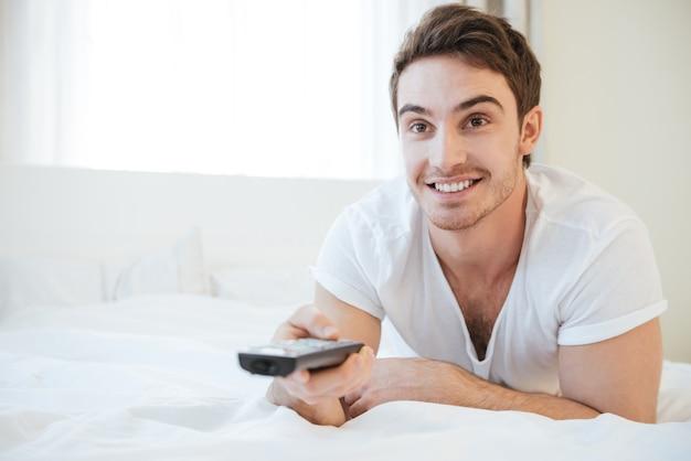 Uomo felice sdraiato sul letto e guarda la tv