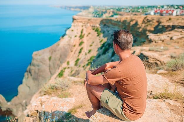 L'uomo felice all'aperto sul bordo della scogliera gode della vista sulla roccia superiore della montagna