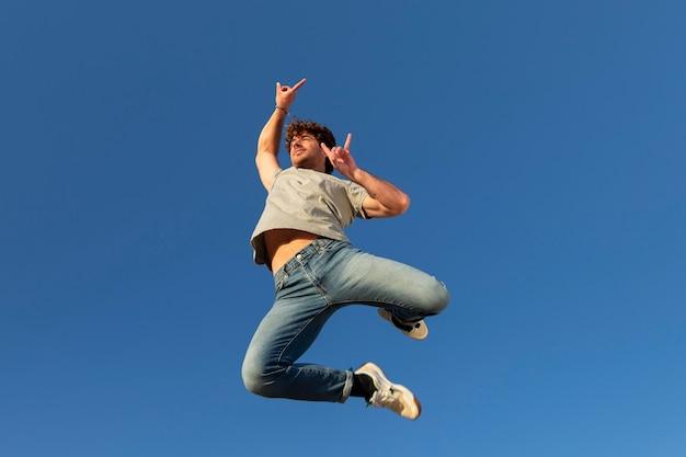 Uomo felice all'aperto che salta in piedi