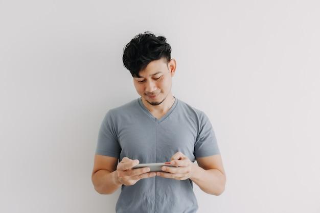 L'uomo felice gioca al gioco mobile online isolato su sfondo bianco