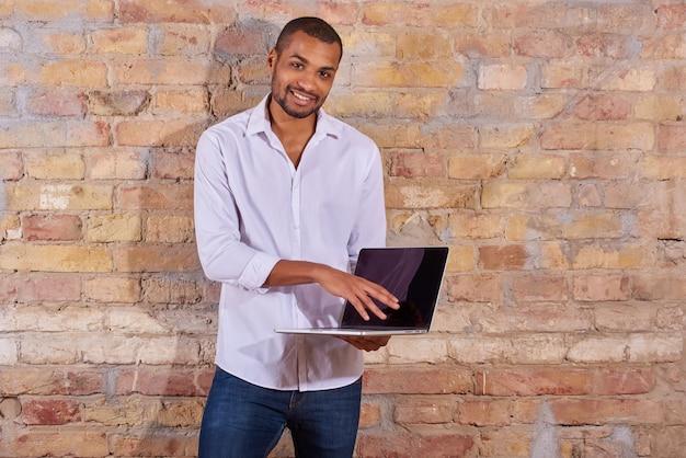 Uomo felice che punta a un computer portatile