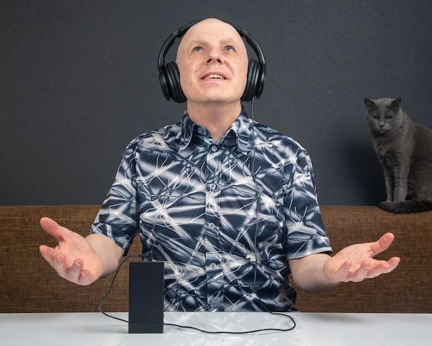 L'uomo felice in cuffie full-size portatili ascolta la musica utilizzando un lettore digitale.
