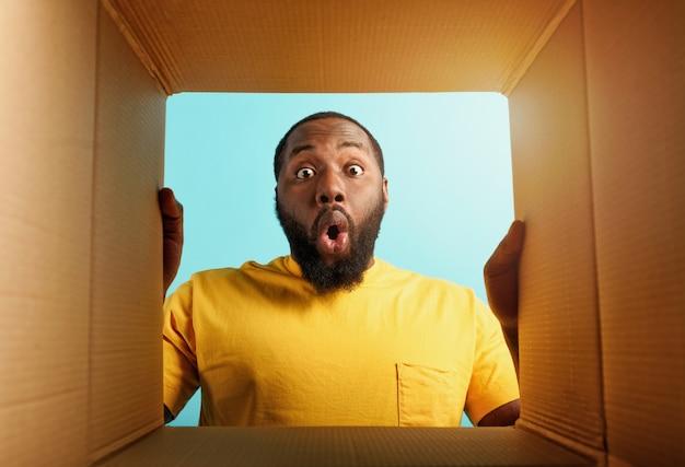 L'uomo felice riceve un pacchetto dall'espressione felice e sorpresa di ordine negozio online