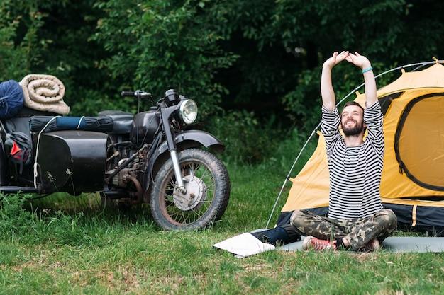 Uomo felice che si distende nella foresta la mattina d'estate