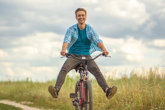 L'uomo felice va in bicicletta in un campo