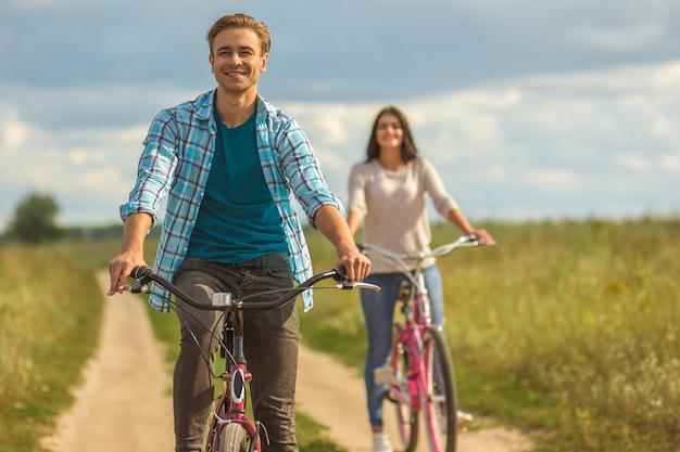 L'uomo felice in sella a una bicicletta vicino alla donna all'aperto