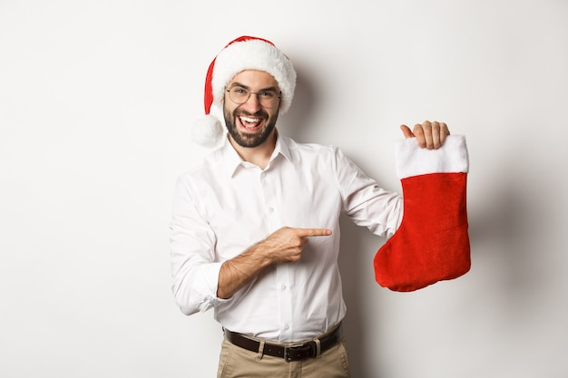 Uomo felice in cappello della santa che celebra le vacanze invernali, indicando il calzino di natale e sorridente, tenendo i regali, in piedi su sfondo bianco.
