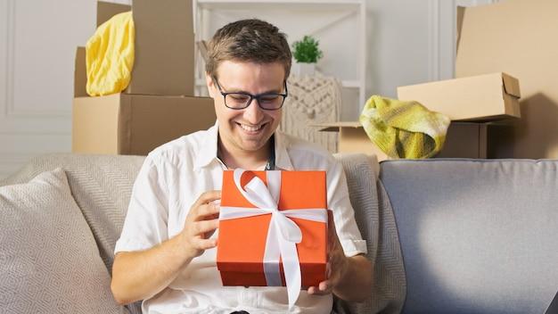 Un uomo felice soddisfatto da una consegna rapida disimballaggio dell'ordine dai negozi online