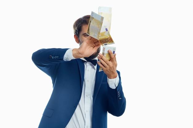 Felice uomo spargere soldi sulla luce muro vestito modello finanza aziendale.