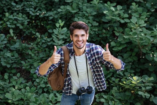 L'uomo felice in camicia con binocolo e zaino nella foresta mostra le dita in su