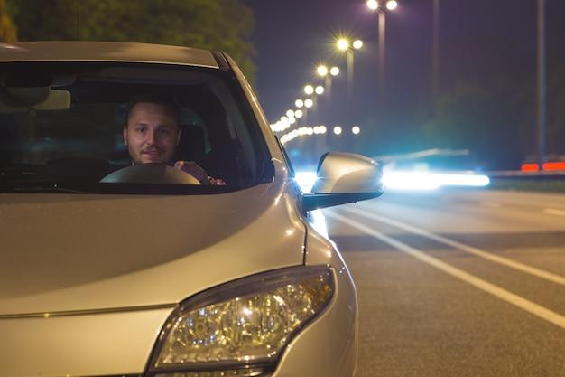 L'uomo felice si siede all'interno dell'auto in autostrada. sera notte