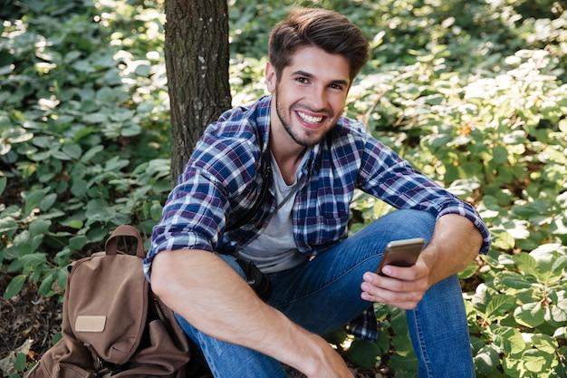 Uomo felice seduto nella foresta