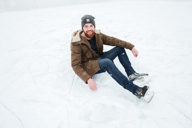 Uomo felice seduto sulla neve con i pattini da ghiaccio