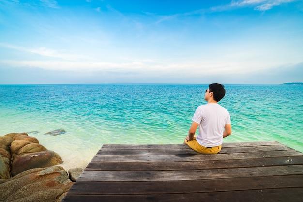 Felice l'uomo seduto su un ponte di legno nella spiaggia del mare a koh munnork island, rayong, thailandia