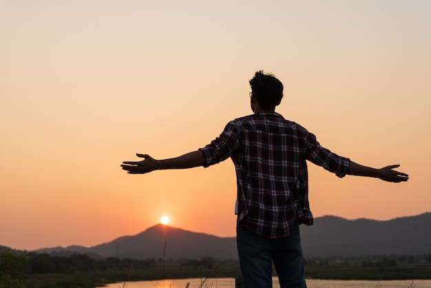 Uomo felice che spande le braccia per le emozioni di libertà.