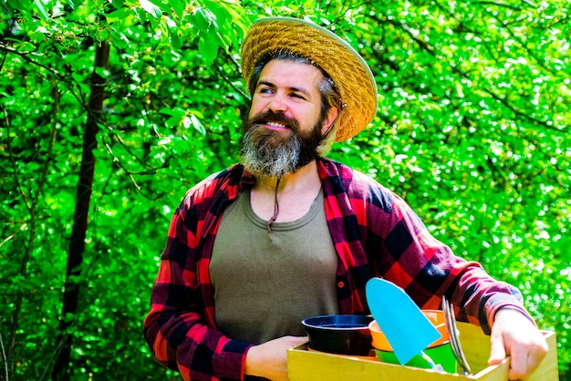 Uomo felice nel giardino di primavera. giardiniere in fattoria ecologica con piantagione di attrezzi da giardinaggio.