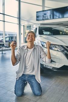 L'uomo felice sta sulle ginocchia che si rallegra l'acquisto di una nuova auto in showroom