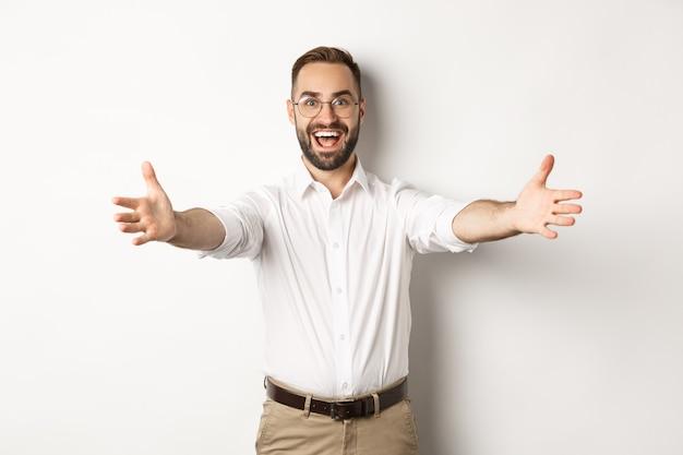 Uomo felice che allunga le mani in un caloroso benvenuto, aspettando un abbraccio o salutando qualcuno, in piedi su uno sfondo bianco.