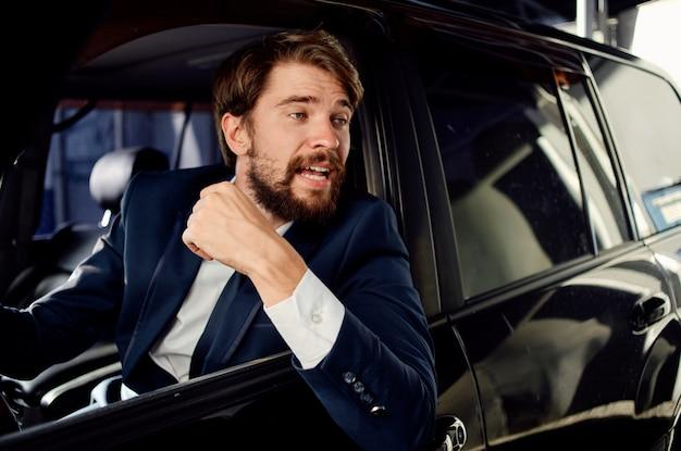 Uomo felice in vestito guarda fuori dal finestrino della macchina e gesticola con le mani