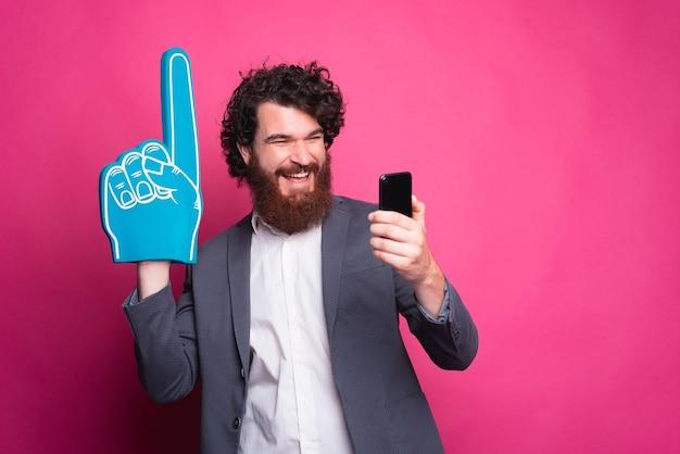 Uomo felice che sostiene la sua squadra preferita, uomo barbuto eccitato in casual utilizzando il telefono e indicando con il guanto del ventilatore