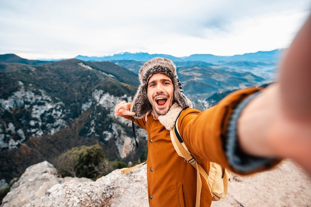Uomo felice che cattura un selfie scalando le montagne