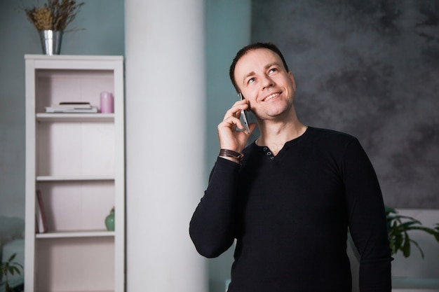 Uomo felice che parla al telefono in ufficio, sorridente al posto di lavoro, successo e soddisfazione.