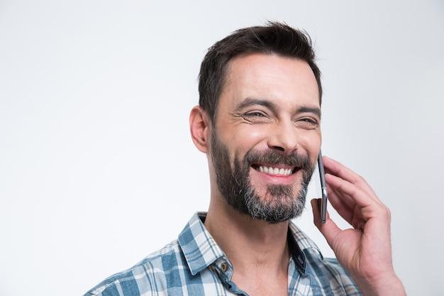 Uomo felice che parla al telefono isolato su un muro bianco