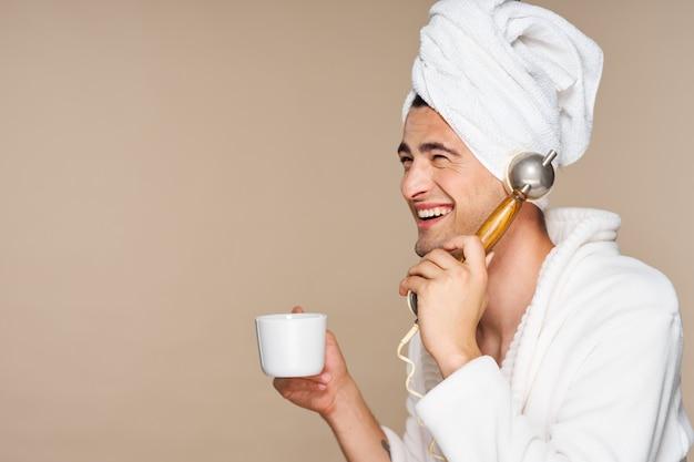 Uomo felice che parla al telefono con una tazza di caffè e un asciugamano