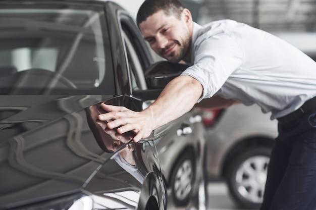 Uomo felice che tocca auto in auto show o salone.