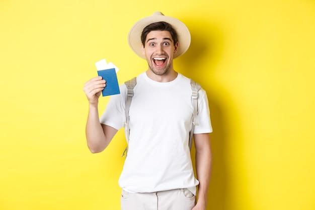 Turista dell'uomo felice che mostra il suo passaporto con i biglietti, andando in viaggio, in piedi sopra il muro giallo con lo zaino.