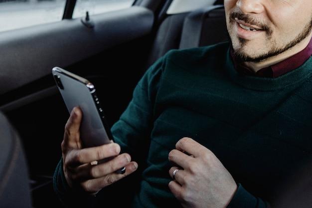 Uomo felice che usa il suo smartphone in macchina