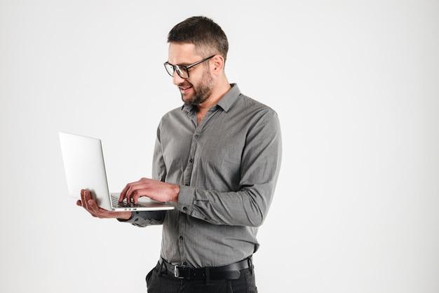 Uomo felice che per mezzo del computer portatile.
