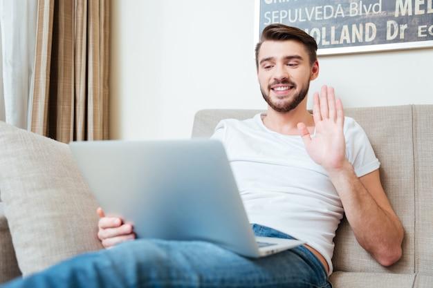 Video chat uomo felice sul computer portatile sul divano di casa
