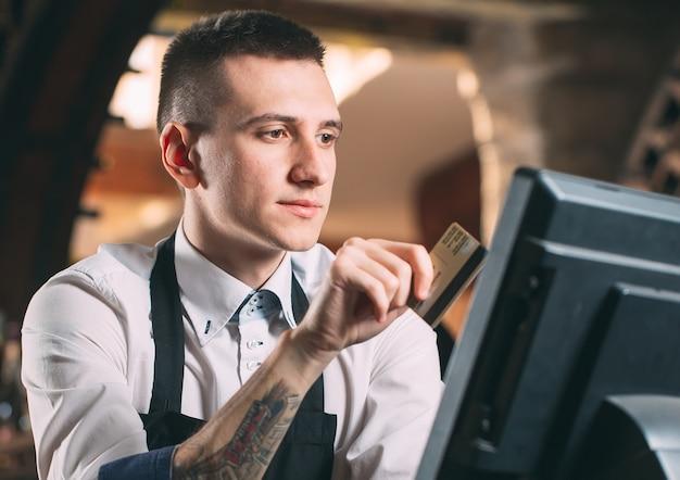 Uomo felice o cameriere in grembiule al bancone con cassa lavorando al bar o alla caffetteria