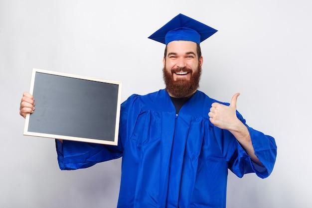 Uomo felice che indossa scapolo blu che mostra lavagna nera e mostra pollice in su