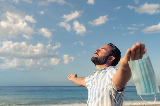 Uomo felice che indossa maschera medica all'aperto contro il cielo blu sullo sfondo
