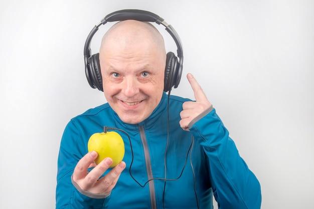 L'uomo felice che porta le cuffie a grandezza naturale portatili ascolta la musica usando un giocatore della mela.