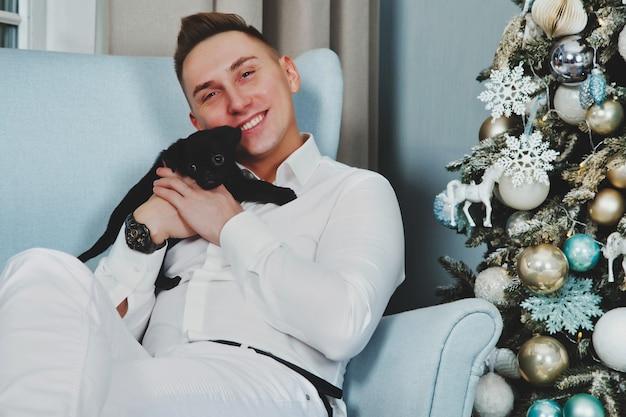 Uomo felice in abiti bianchi con un simpatico cane di razza grifone irlandese nero seduto su una sedia all'albero di natale in soggiorno per buon natale e felice anno nuovo. momenti caldi d'atmosfera in famiglia con regali